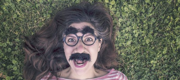 Woman with glasses with thick eyebrows and mustache