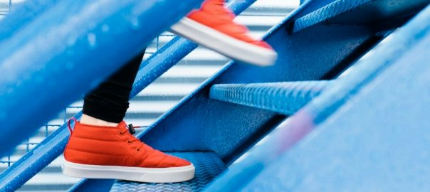 Orange Shoes walking up blue stairs